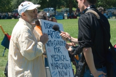 Man with medical marijuana sign is being interviewed