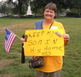 "Woman holding sign saying ""Keep my son in his home."""