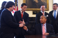 Governor Patrick gives Rose a pen while Treasurer Grossman talks.