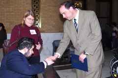 Ben, a MWCIL consumer, shakes hands with State Senator James Eldridge, while Pat, an IL Coordinator at MWCIL, looks on.
