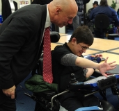 Sam shows Representative Tom Sannicandro how his DynaVox communication device works.