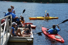 people on dock and in kayaks