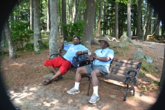 two men relax on a bench