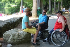 three people talk in the shade