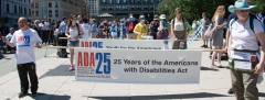 marchers with banner - 25 years of the americans with disabilities act