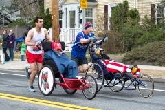 Two men pushing wheelchairs