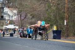 Two women wheelchair racers coming up the hill