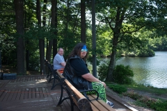 2 people sitting on a bench overlooking the pond