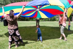 Kids and Adults play with large parachute.