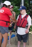 DCR staff helps one person with his life jacket