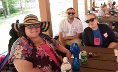 Three people enjoy the pavilion shade