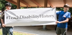 Ben (r) and friend hold the Teach Disability History campaign banner