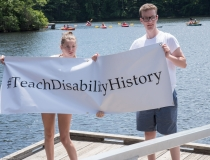 two people holding Teach Disability History campaign banner