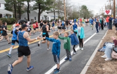 Kids high fiving runners