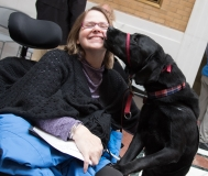 Woman with guide dog licking her face
