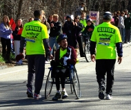Bill Reilly in wheelchair facing backwards with two guides