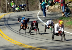 several wheelchair racers going downhill
