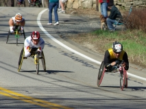 three wheelchair racers going downhill