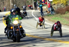 several wheelchair racers going downhill and police motorcycle