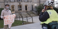"""Advocate with Sign """"No Light Show at Fernald"""" educates woman on her bike."""