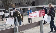 """Protestors at Fernald - banner saying Human Rights Not Holiday Lights.  Sign saying """"Don't"""""""