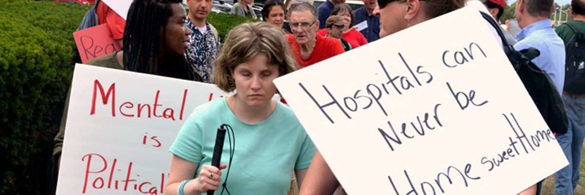 demonstrators - signs say Hospitals can never be Home Sweet Home